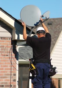 Worker installing satellite dish