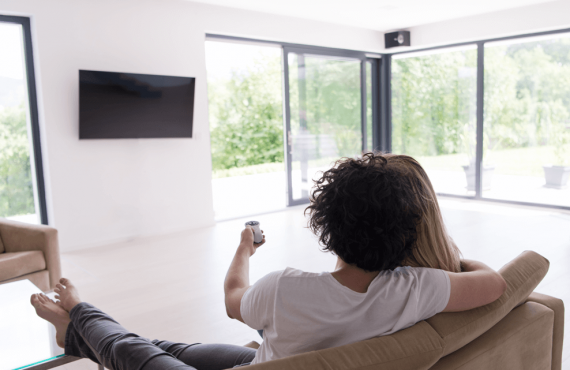 rear-view-of-couple-watching-television-PGVRFWB